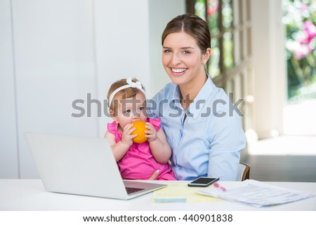 Happy woman sitting with baby by table at home - stock photo