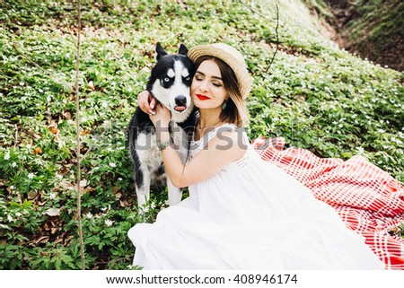 happy woman sleeps with her pet on the green grass - stock photo