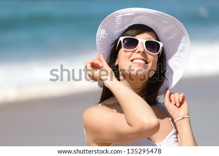 Happy woman smiling and enjoying on summer beach vacation. Beautiful caucasian girl in holidays, wearing white sunglasses and hat on sea background. Copy space. - stock photo