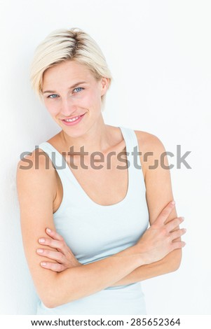 Happy woman smiling at camera with arms crossed on white background - stock photo