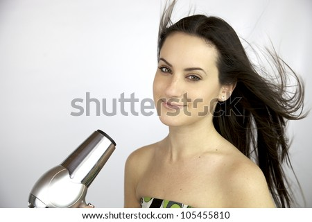 Happy woman smiling while blow dryer send air on her long hair - stock photo