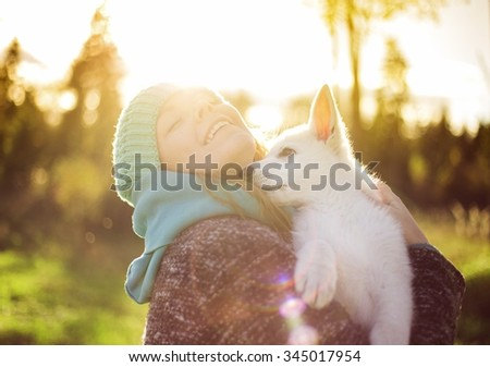 happy woman smiling with a white puppy dog in the park at sunset - stock photo