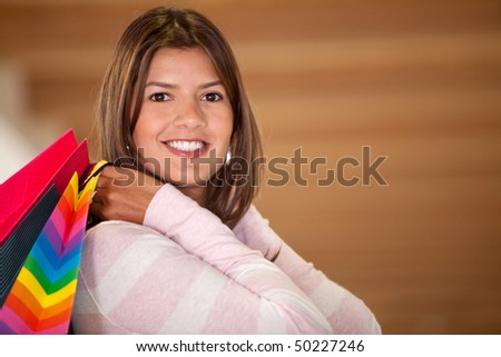happy woman smiling with shopping bags in a mall - stock photo