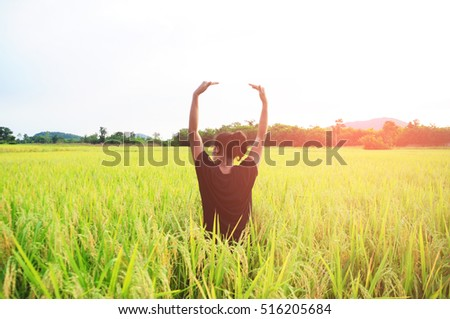 happy woman stand at rice field with sunlight. soft focus