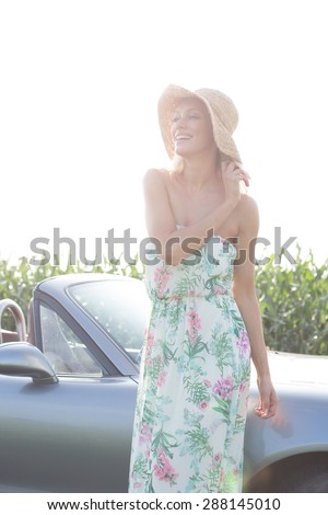 Happy woman standing by convertible against clear sky