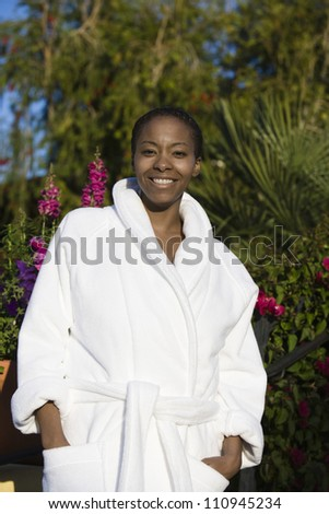 Happy woman standing in bathrobe - stock photo
