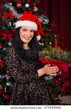Happy woman standing near tree and holding Christmas arrangement - stock photo