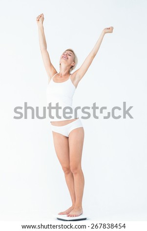 Happy woman standing on a scales spreading her arms on white background - stock photo