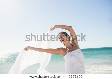 Happy woman standing on the beach - stock photo