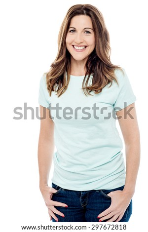 Happy woman standing with hands in pockets - stock photo