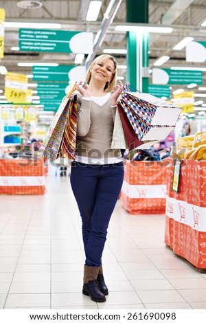 Happy woman standing with shopping bags on the store - stock photo