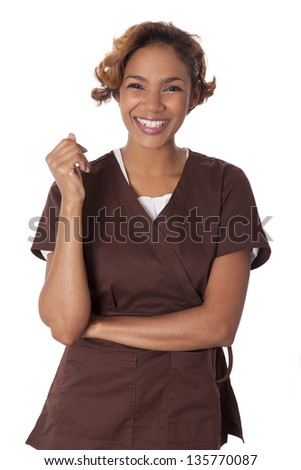 Happy woman stands smiling in scrubs, isolated on white background.