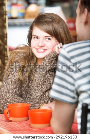 Happy woman staring at man in cafe