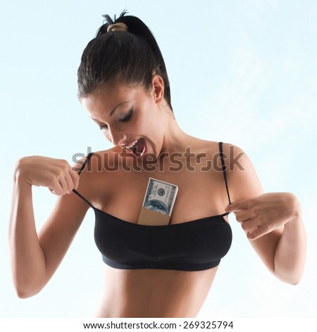 happy woman stretching brassrie , holding dollars between her breast-grain added - stock photo