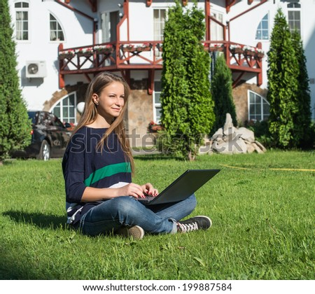 Happy woman student sitting on grass with laptop. Beautiful casual female outdoor using pc. - stock photo