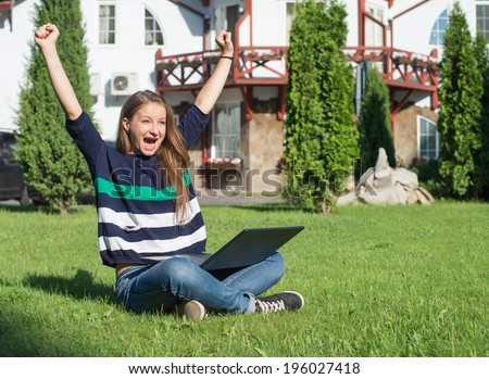 Happy woman student with arms lifted in joy sitting on grass with laptop. Successful girl online. Winning success woman happy ecstatic celebrating being a winner. - stock photo