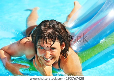 Happy woman  swimming on inflatable beach mattress.