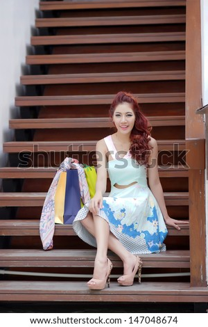 Happy woman taking a break with shopping bags while sitting on the stairs, Model is Thai Ethnicity.