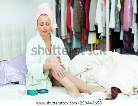 Happy woman taking care of leg skin after shower