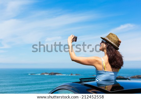 Happy woman taking selfie photo with smartphone camera on car summer travel vacation to the coast. Brunette girl  leaning out vehicle sunroof towards the sea. - stock photo