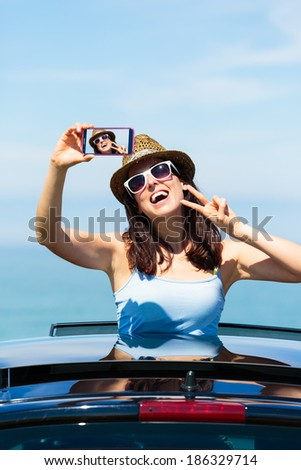 Happy woman taking smartphone selfie photo on car summer travel vacation to the coast. Brunette girl  leaning out car sunroof with the sea on background. - stock photo