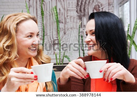 happy woman talking and drinking coffee in a small cafe
