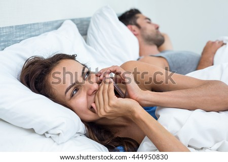 Happy woman talking phone on bed with husband sleeping in background