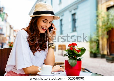 Happy woman talking the phone sitting in outdoors cafe in european city