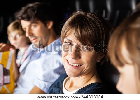 Happy woman talking to daughter while watching movie with family in cinema theater - stock photo