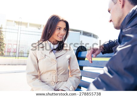Happy woman talking with man outdoors. Sitting on the bench. Looking at each other - stock photo