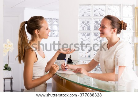 Happy woman talks with secretary in the office of women hospital - stock photo