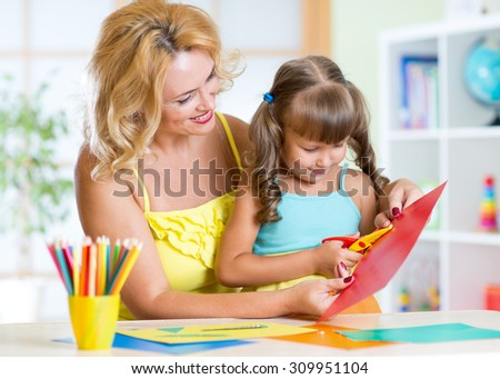 Happy woman teaching preschooler kid do craft items in day care center - stock photo