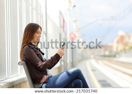 Happy woman texting on a smart phone in the train station with the railway in the background - stock photo