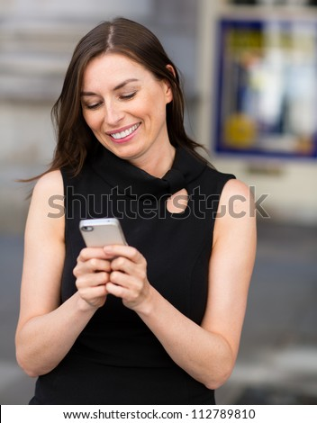 Happy woman texting on her cell phone and smiling - stock photo
