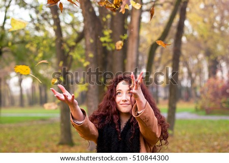 Happy woman throwing up autumn leaves in the air, smiling and cheerful in autumn park