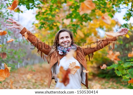 Happy woman throws autumn leaves in the park