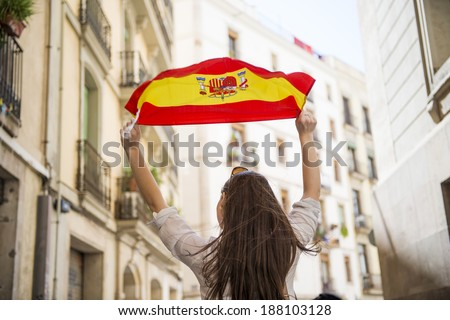 Happy woman tourist is walking in the city street of Barcelona with spanish flag. - stock photo