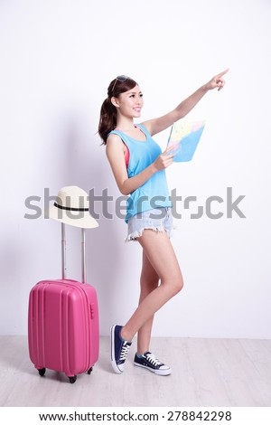 Happy woman tourist travel holding map and finger pointing something with white concrete wall and wood floor, asian beauty - stock photo