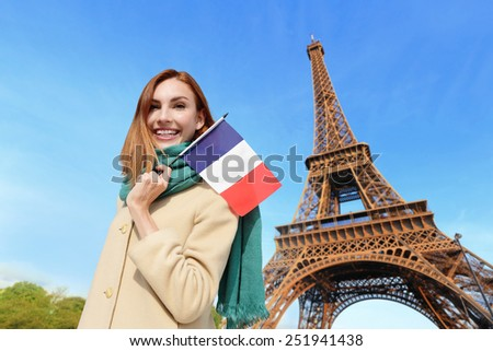 Happy woman travel in Paris with eiffel tower and beautiful blue sky and holding France French flag, caucasian beauty - stock photo