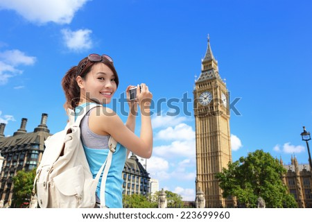 Happy woman traveler photo by camera in London with Big Ben tower,  London, UK,  asian beauty - stock photo