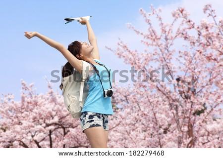 Happy woman traveler photo by camera with sakura tree on vacation in japan - stock photo