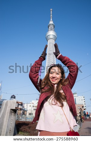 Happy woman traveler show hand gesture with Tokyo Sky Tree building on vacation in japan. - stock photo