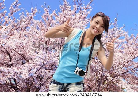 Happy woman traveler show thumb up with sakura tree on vacation in japan, asian - stock photo