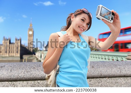 Happy woman traveler take photo selfie by camera in London with Big Ben tower,  London, UK,  asian beauty - stock photo