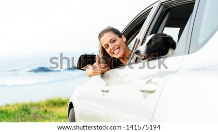 Happy woman traveling in car with dog. Happy woman on road trip with her pet out of the auto window towards coast landscape background.