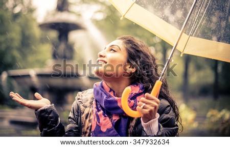 Happy woman under the rain smiling holding the umbrella - stock photo