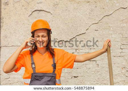 Happy woman unloading sand for construction and talking on a phone