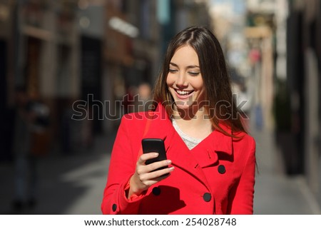 Happy woman using a smart phone while is walking in the street in a sunny day - stock photo