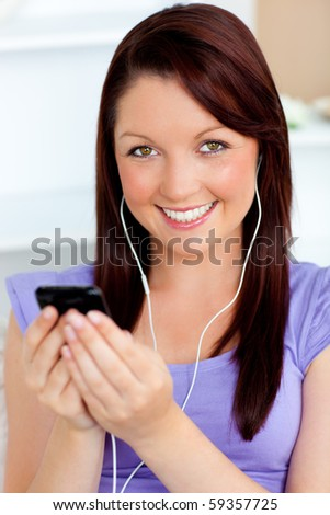 Happy woman using her cellphone to listen to music with earphones at home