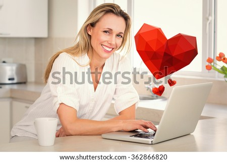 Happy woman using laptop at counter against heart - stock photo